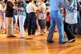 Wiele szczęśliwych par starszych zakochanych tańczy na drewnianym parkiecie.