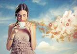 Piękna młoda kobieta trzyma filiżankę herbata nad nieba tłem