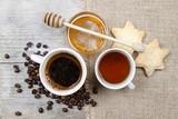 Filiżanka kawy, filiżanka herbata i puchar miód na drewnianym stole.