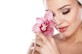 młoda kobieta z ręcznikiem na głowie pozowanie z orchidei