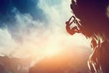 Sylwetka człowieka wspinaczka na skale, góra o zachodzie słońca.
