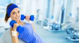 Młoda szczęśliwa kobieta robi sprawności fizycznej ćwiczeniu przy gym ,.