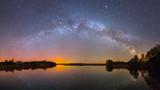 Jaskrawa Droga Mleczna nad jeziorem nocą (zdjęcie panoramiczne)