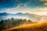 Niesamowity krajobraz górski z mgłą i stogu siana