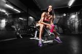 dziewczynka fitness z shaker pozowanie na ławce na siłowni