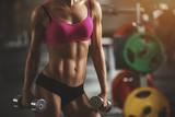 Brutalna sportowa kobieta pompuje up mięśnie z dumbbells