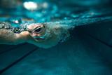 Mężczyzna pływaczka przy pływackim basenem. Podwodna fotografia.