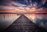 Wspaniały zachód słońca nad jeziorem z łodzi i drewnianym molo
