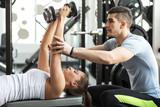 Instruktor fitness, ćwiczenia z klientem na siłowni