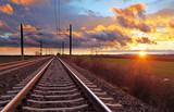 Pomarańczowy zmierzch w niskich chmurach nad linią kolejową