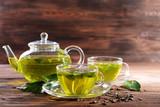 Filiżanki zielona herbata na stole na drewnianym tle