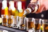 Barman wlewa twardego ducha w szklanki