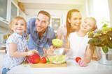 Rodzina w kuchni robi świeżą sałatkę