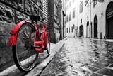 Retro rocznika czerwony rower na brukowiec ulicie w starym miasteczku. Kolor w czerni i bieli
