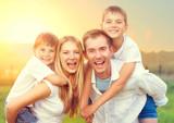 Szczęśliwa młoda rodzina z dwójką dzieci na polu pszenicy latem