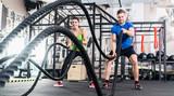 Kobieta i mężczyzna na siłowni z liny bitwy