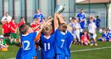 Młoda drużyna sportowa z trofeum. Boys Celebrating Sports Achievement. Młodzi gracze piłki nożnej trzyma trofeum. Świętujemy Mistrzostwa w piłce nożnej. Zwycięski zespół turnieju sportowego dla dzieci dzieci.