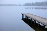 Mglisty wschód słońca nad jeziorem. Piękny stary drewniany molo, most dla łowić i lasowy wzgórze w tle. Malowniczy naturalny krajobraz. Koncepcja wakacje.