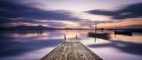 Perspektywiczny widok drewniany molo w lagunie przy zmierzchem z doskonale uspokaja wodę i odbicie