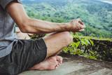 Młody modny mężczyzna medytuje w gazebo na tle