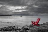 Czerwone krzesło kontrastujące z czarnym i białym tle oceanu.