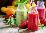 Wielobarwne butelki ze świeżymi owocowymi koktajlami z pasiastą ul