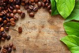 Kawa na drewnianym tle z zielonymi liśćmi