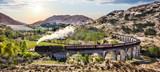 Glenfinnan Kolejowy wiadukt w Szkocja z Jacobite kontrpary pociągiem przeciw zmierzchowi nad jeziorem
