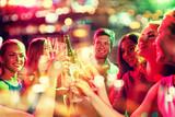 uśmiechnięci przyjaciele z kieliszkami do wina i piwem w klubie