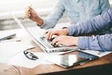 Strona internetowa przedsiębiorcy budowlani pracuje używać laptop przy biurem na drewnianym