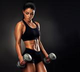 Pięknej sprawności fizycznej kobiety podnośni dumbbells. Sprawności fizycznej sporty kobieta pokazuje ona well - wyszkolony ciało. Ciało pięknej dziewczyny z falującymi mięśniami od treningu siłowego.