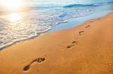 plaża, fala i ślady stóp w czasie zachodu słońca