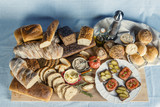 Stół zastawiony chlebem, warzywami, smalcem i przyprawami na śniadanie w kompozycji na tle obrusu