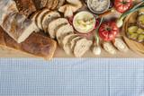 Stół zastawiony chlebem, pomidorami, cebulkami i smalcem na śniadanie na stole z obrusem w kratę