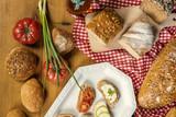 Pełnoziarnisty chleb, pomidory, szczypiorek i gotowe kanapki na drewnianym stole