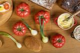 Drewniany stół zastawiony pomidorami, cebulkami, chlebem i masłem, kompozycja