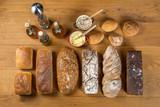 Widok z góry na aranżację chlebów i bułek oraz dodatki w postaci masła, smalcu i oliwy