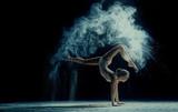 Pełen wdzięku kobieta tańczy w chmurze pyłu