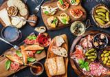 Zestaw przekąsek włoskich antipasti. Brushetta, odmiana sera, oliwki śródziemnomorskie, marynaty, szynka parmeńska z melonem, salami i wino w szklankach na czarnym tle grunge, widok z góry