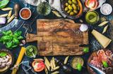 Włoscy karmowi kulinarni składniki na ciemnym tle z nieociosaną drewnianą ciapanie deską w centrum, odgórny widok, kopii przestrzeń