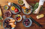 Cropped wizerunek kobiety ręki tnący warzywa przy drewnianym stołem