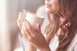Piękna młoda kobieta z filiżanką kawy w domu