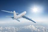 Duży płaski latanie w kierunku z słońcem w niebieskim niebie