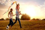 Rodzina z córką biegnie i puszcza latawce