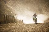 Motocyklista wyścigi konne przez polną drogę.