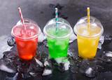 kolorowe zimne napoje w plastikowych kubkach z lodem