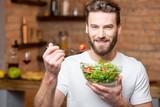 Przystojny brodaty mężczyzna w białej koszulki łasowania sałatce z pomidorami w kuchni. Koncepcja zdrowej i wegańskiej żywności