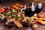 Zestaw przekąsek włoskich antipasti. Odmiana sera, śródziemnomorskie oliwki, marynaty, szynka parmeńska, pomidory, karczochy i wino w szklankach