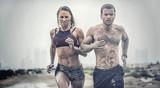 Mięśni sportowiec płci męskiej i żeńskiej pokryte w błocie biegnącej w trudnym terenie z pustynnym tle w wyścigu sportów ekstremalnych