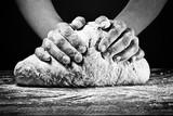 Ręce kobiety wyrabiania ciasta. W czarno-białym stylu na ciemnym tle.